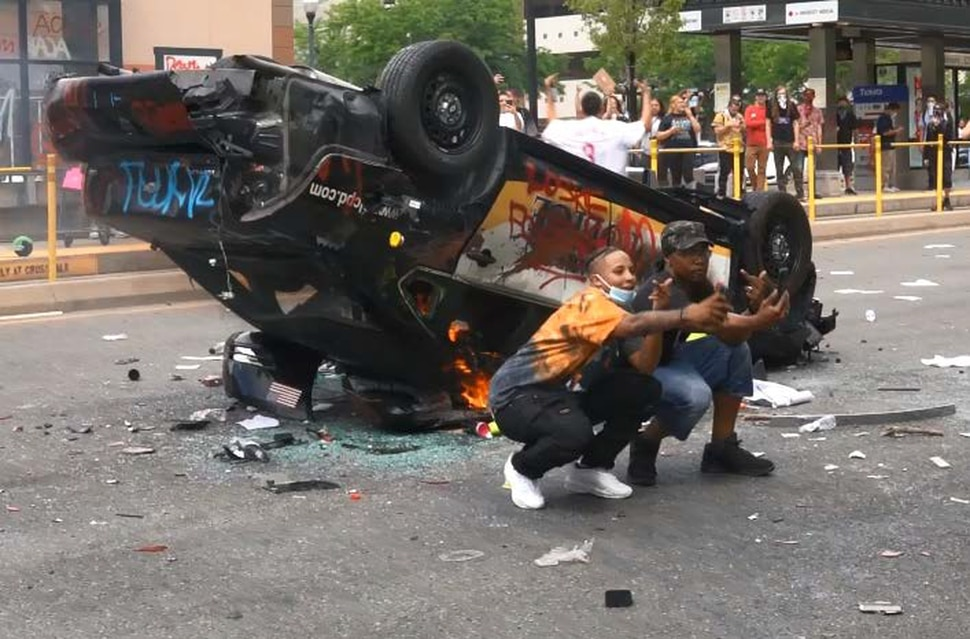 (Photo courtesy of the U.S. Attorney's Office) A person identified as Lateesha Richards of Salt Lake City takes a selfie alongside a man identified as Latroi Newbins in front of an overturned and burning Salt Lake City Police Department car on May 30, 2020, in Salt Lake City. Richards and Newbins have been charged with felony arson.