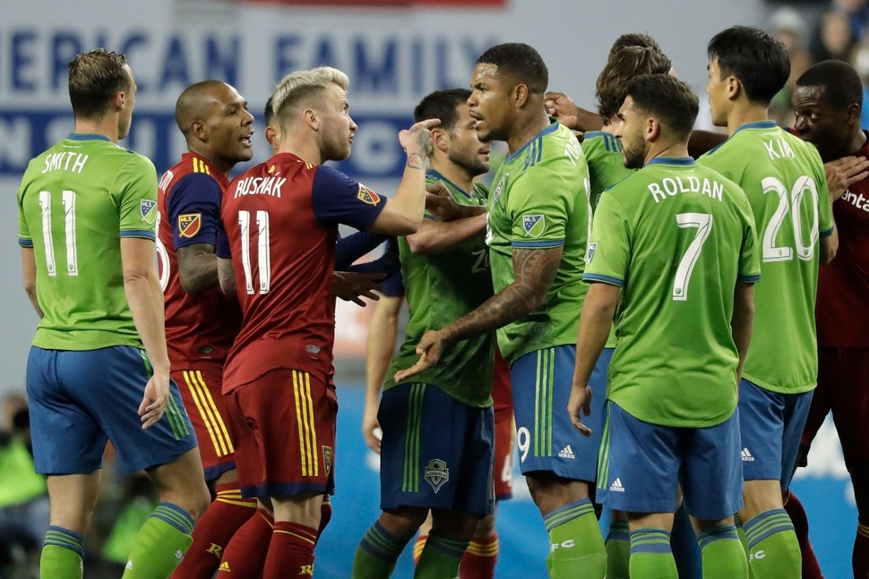 Seattle Sounders and Real Salt Lake players, including RSL's Albert Rusnak (11) and Sounders' Roman Torres, third from right, scuffle during the first half of an MLS Western Conference semifinal playoff soccer match Wednesday, Oct. 23, 2019, in Seattle. (AP Photo/Ted S. Warren)