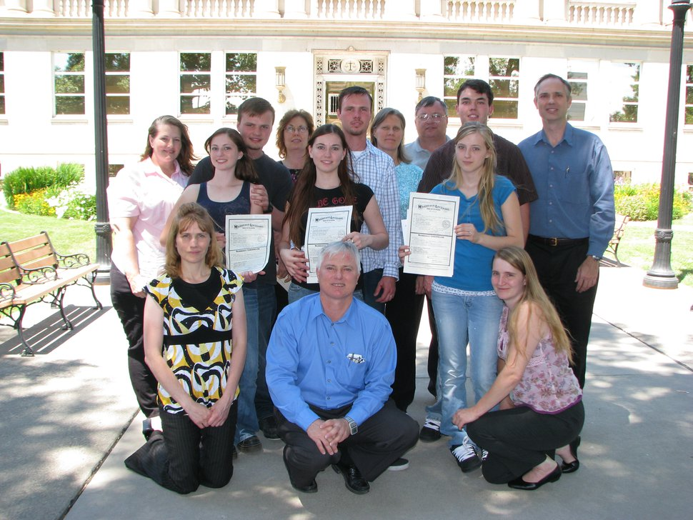 (Photo courtesy Shanell DeRieux) John Daniel Kingston, front center, kneels in front of three of his daughters as they hold their wedding certificates July 3, 2008, in Grand Junction, Colo. Shanell DeRieux, second row left, was 18; the other two girls were 16. Each daughter married one of their cousins, who also are pictured with their parents. Three of Kingston's 14 wives also are in the photo. All the families belong to the Davis County Cooperative Society. While the sect is headquartered in Utah, members will travel to Colorado to wed because cousin marriages are legal there.