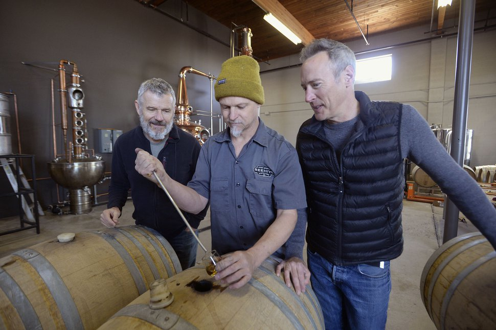 (Al Hartmann | The Salt Lake Tribune) Matt Aller, left, Chris Barlow, and Erik Ostling co-owners of Beehive Distilling, check on the Barrel Reserve Gin at their new Salt Lake City location at 2245 S. West Temple. The new 450-gallon copper still in the background will allow the team to increase production.