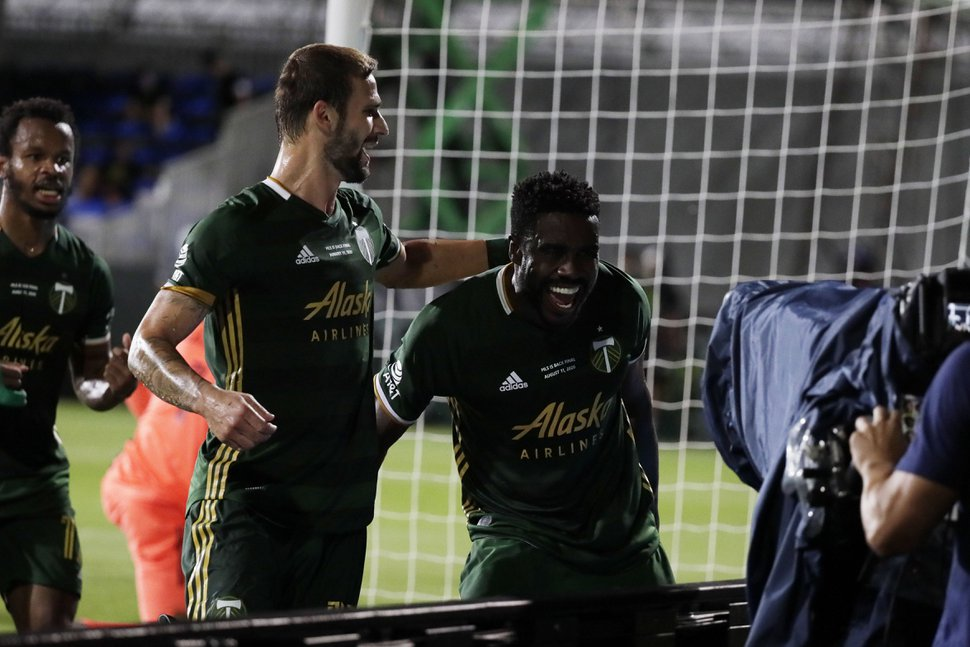 Orlando City forward Tesho Akindele (13) congratulates defender Larrys Mabiala (33) after Mabiala scored a goal, during the first half of an MLS soccer match, Tuesday, Aug. 11, 2020, in Kissimmee, Fla. (AP Photo/John Raoux)