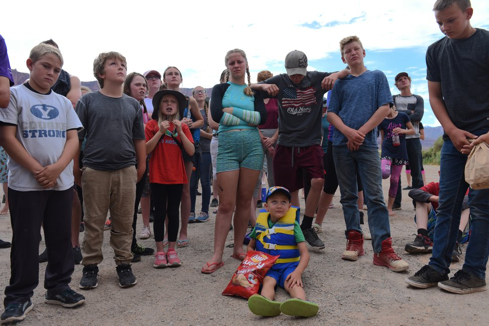 (Shannon Mullane for High Country News) Rally-goers look up at Enoch Foster, who is standing on top of a trailer, as he goes over rafting safety and logistics before leading a prayer near Moab, Utah, on July 27.