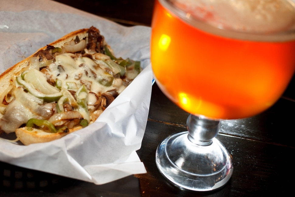 (Trent Nelson | Tribune File Photo) The Philly Cheesesteak sandwich and a schooner of beer at Spedelli's in Salt Lake City.