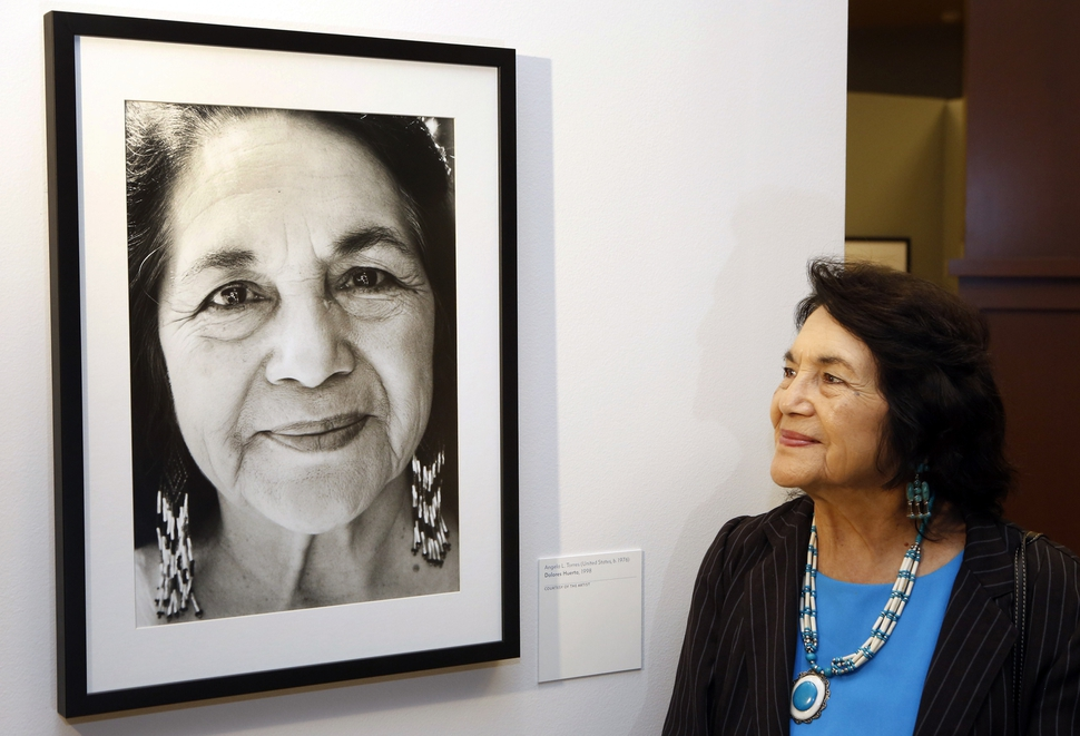 FILE - In this April 10, 2014, file photo, Dolores Huerta, co-founder of United Farms Workers stands by a portrait of herself taken in 1998 by photographer Angela Torres, as she tours her exhibition, Viva la Causa! Dolores Huerta and the Struggle for Justice, at La Plaza de la Cultura y Artes museum downtown Los Angeles. Huerta, the social activist who formed a farm workers union with César Chávez and whose Si, Se Puede chant inspired Barack Obama's 2008 presidential campaign slogan, is the subject of a new PBS documentary. The film Dolores examines the life of the New Mexico-born Mexican-American reformer from her time as a tireless United Farm Workers leader and a campaign volunteer for Sen. Robert Kennedy's 1968 presidential run. (AP Photo/Damian Dovarganes, File)