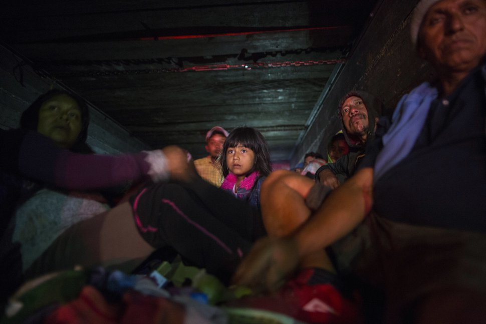 Central American migrants, part of the caravan hoping to reach the U.S. border, travel during the night on a truck in Orizaba, Veracruz state, Mexico, Saturday, Nov. 3, 2018. (AP Photo/Rodrigo Abd)
