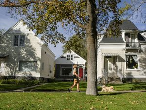 (Leah Hogsten  |  The Salt Lake Tribune) A woman walks her dog in a Salt Lake City neighborhood in October 2020. Utahns struggling to find affordable housing in Utah may find it even harder if they have pets.