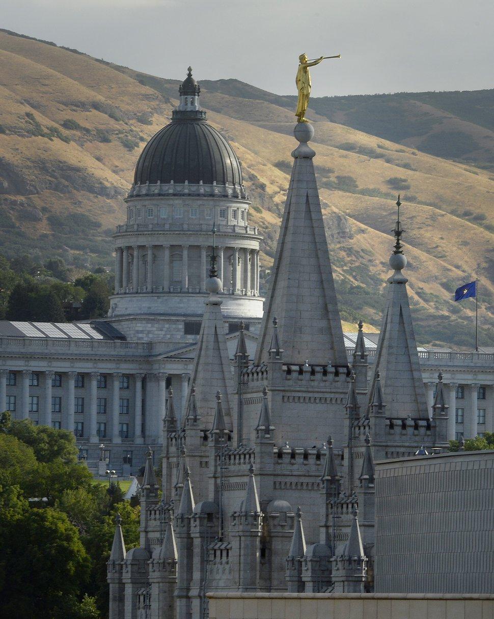 (Scott Sommerdorf/The Salt Lake Tribune) In this July 26, 2017, photo, the Angel Moroni statue sits atop the Salt Lake Temple at Temple Square with the Utah Capitol in the background in Salt Lake City.
