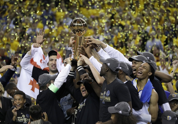FILE - In this June 12, 2017, file photo, Golden State Warriors players, coaches and owners hold up the Larry O'Brien NBA Championship Trophy after Game 5 of basketball's NBA Finals between the Warriors and the Cleveland Cavaliers in Oakland, Calif. Winners of the NBA title in two of the last three seasons, Golden State made it look easy at times a year ago and prevailed in 31 of its final 33 games. (AP Photo/Marcio Jose Sanchez, File)
