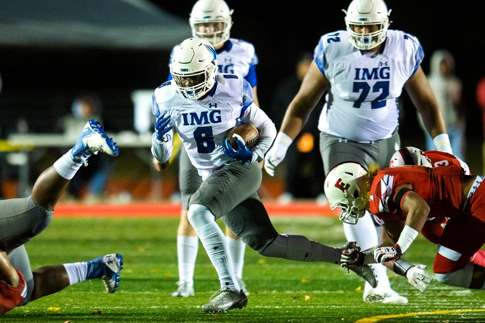 (Chris Detrick | The Salt Lake Tribune) IMG Academy's Trey Sanders (6) runs for a touchdown past East's Viliami Tausinga (7) during the game at East High School Friday, October 20, 2017.