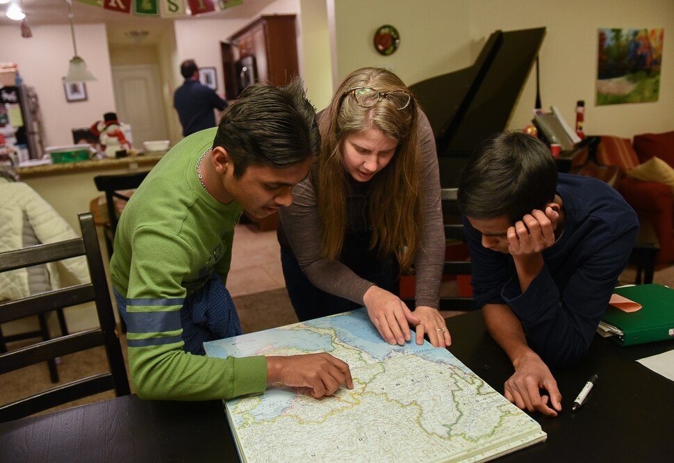 (Francisco Kjolseth | The Salt Lake Tribune) Stephanie Santarosa, center, is joined by her Burmese foster boys Faisal, 18, left, and Rohim, 14, as they look over maps in search of their homes of origin. For the Santarosa family they can't imagine life without their Rohingya Muslim sons from Myanmar - also known as Burma.