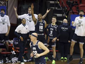 The Utah State bench reacts as Utah State guard Brock Miller (22) sinks a 3-point shot during the first half of an NCAA college basketball game against San Diego State in the championship of the Mountain West Conference men's tournament Saturday, March 13, 2021, in Las Vegas. (AP Photo/Isaac Brekken)