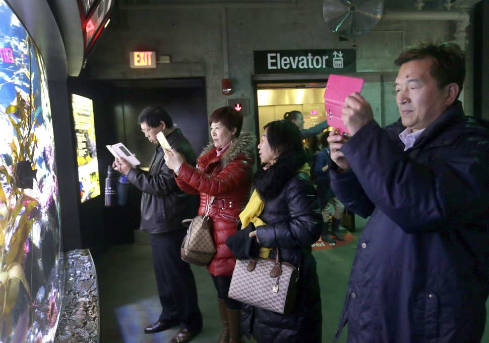 In this March 27, 2017 photo, tourists from China take pictures at the New England Aquarium in Boston. In cities across the country, the American hospitality industry is stepping up efforts to make Chinese visitors feel more welcome. (AP Photo/Elise Amendola)