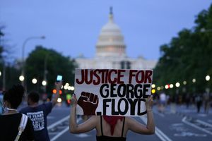 FILE - In this May 29, 2020, file photo, Demonstrators walk along Pennsylvania Avenue in Washington as they protest the death of George Floyd, a black man who died in police custody in Minneapolis.  (AP Photo/Evan Vucci, File)