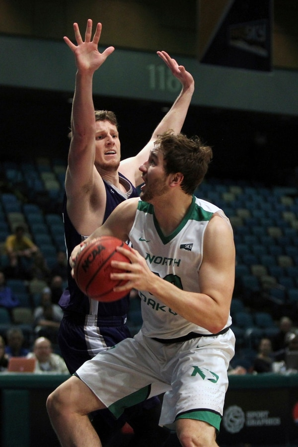 North Dakota forward Conner Avants (32) shoots in front of Weber State guard Dusty Baker (25) during the first half an NCAA college basketball game in the final of the Big Sky tournament in Reno, Nev., Saturday, March 11, 2017. (AP Photo/Lance Iversen) .