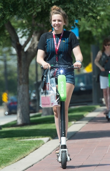 (Rick Egan | The Salt Lake Tribune) Becca Emter, from Helena Montana, rides a Lime Scooter South Temple, in Salt Lake City, Monday, July 30, 2018.
