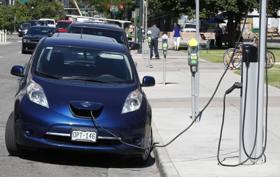(David Zalubowski | AP file photo) A Nissan Leaf charges at a recharge station while parked by the Denver City County Building in downtown Denver in 2018.