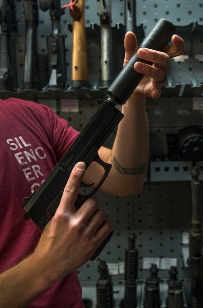 Leah Hogsten | The Salt Lake Tribune Silencerco's public relations specialist Matt Pinnell places Silencerco's Omega K silencer on a .45 caliber pistol in the company's gun safe. Silencerco is one of the country's largest manufacturers of silencer for guns of all kinds, Friday, May 28, 2017.