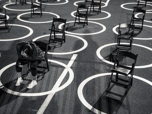 "(Damon Winter | The New York Times)  A staff member for the Biden campaign sits among physically-distanced chairs before an election night rally at the Westin Hotel in Wilmington, Del., on Tuesday, Nov. 3, 2020. ""We might be able to achieve normalcy by summer. Our leaders should embrace the possibility,"" writes New York Times opinion columnist Ross Douthat."