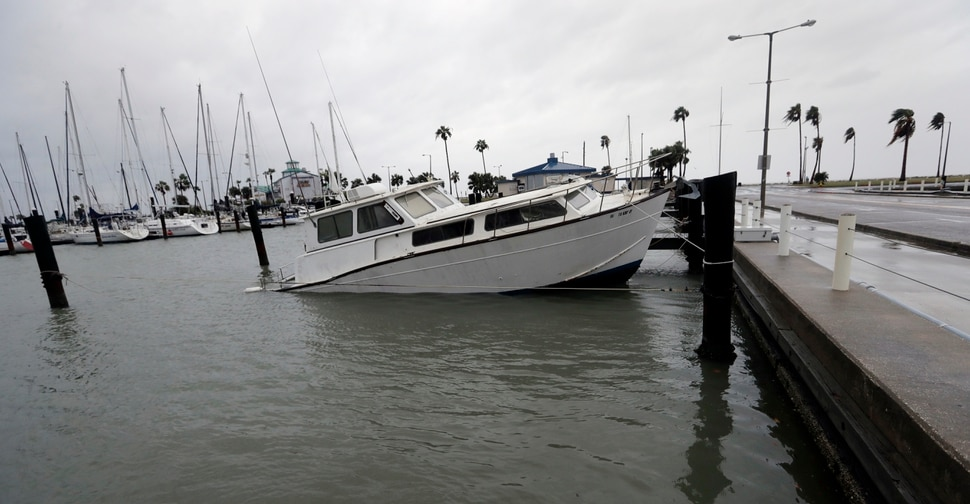(Eric Gay | The Associated Press) A fishing boat is left partial submerged after Hurricane Harvey swept through the area, Saturday, Aug. 26, 2017, in Corpus Christi, Texas. Harvey has been further downgraded to a Category 1 hurricane as it churns slowly inland from the Texas Gulf Coast, already depositing more than 9 inches of rain in South Texas.