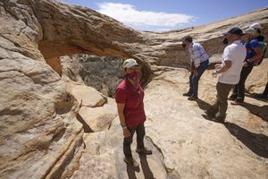 (Rick Bowmer | AP, pool) U.S. Interior Secretary Deb Haaland tours near ancient dwellings along the Butler Wash Trail during a visit to Bears Ears National Monument Thursday, April 8, 2021, near Blanding. At right is Sen. Mitt Romney and Utah Gov. Spencer Cox.