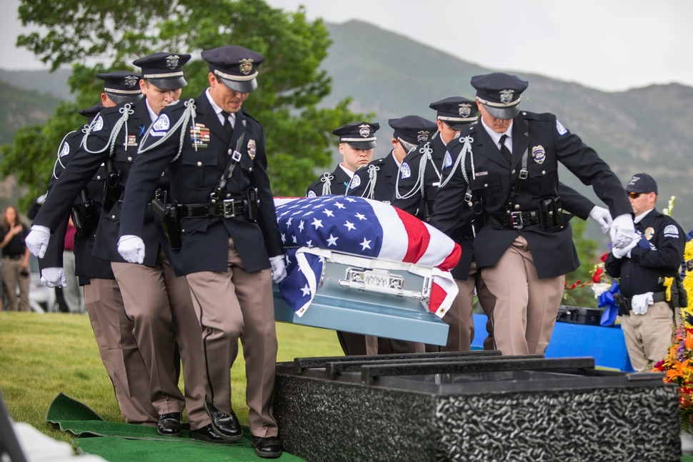 (Ben Dorger/Standard-Examiner via AP)Ogden police officers carry the casket of Ogden Police Officer Nate Lyday to its final resting place at Lindquist's Memorial Gardens of the Wasatch cemetery on Saturday, June 6, 2020, in Ogden, Utah. Lyday's remains were brought in procession on an Ogden fire truck from a funeral service at Lindquist Field. The 24-year-old officer was killed in the line of duty Thursday, May 28, when responding to a domestic violence call.