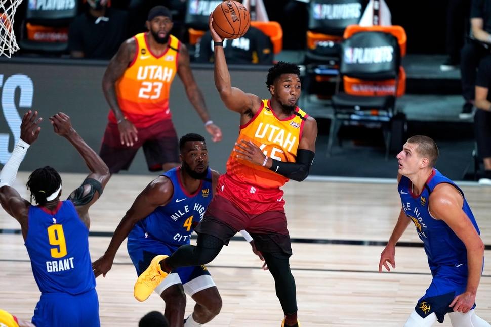 Utah Jazz's Donovan Mitchell (45) passes the as Denver Nuggets' Jerami Grant (9), Paul Millsap (4) and Nikola Jokic, right, defend during the first half of an NBA basketball first round playoff game Sunday, Aug. 23, 2020, in Lake Buena Vista, Fla. (AP Photo/Ashley Landis, Pool)