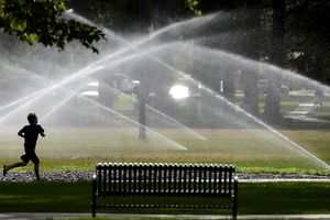 (Tribune file photo) Sprinklers cool down a runner at Liberty Park in Salt Lake City in 2017. Utahns rank among the highest per-capita water users in the nation.