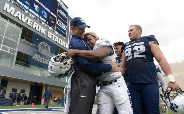 Leah Hogsten | The Salt Lake Tribune Utah State University football team head coach Matt Wells is bear hugged by running back LaJuan Hunt after the team's annual Blue vs. White Spring Game, Saturday, April 8, on Merlin Olsen Field at Maverik Stadium.