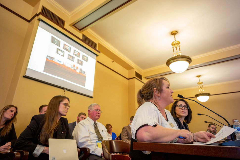 (Trent Nelson | The Salt Lake Tribune) Shirlee Draper of Cherish Families speaks, seated next to Sen. Deidre Henderson, R-Spanish Fork, at the first public hearing for SB102, which would make polygamy between consenting adults an infraction (punishable by a ticket but no arrest or jail time) instead of a felony, on Monday, Feb. 10, 2020. On the screen at upper left is a photo taken in a plural marriage home showing seven of the family's children who have served in the military.