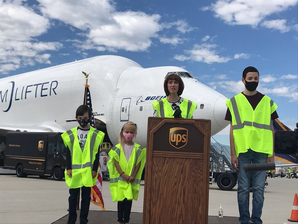 (Nate Carlisle | The Salt Lake Tribune) State Superintendent of Public Instruction Sydnee Dickson speaks in front of a modified Boeing 747 called the Dream Lifter at Salt Lake City International Airport on July 1, 2020. Dickson was joined by students Leyson Bryant, age 6, left, Joanna McConkie, 6, and Tommy Mansell, 14. Everyone on the tarmac was required to wear a safety vest. The airplane, operated by Atlas Air, delivered 500,000 cloth masks to be distributed to schools to slow the spread of the coronavirus.