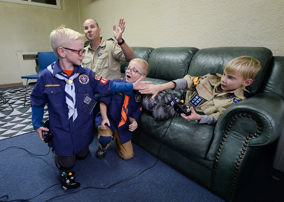 (Francisco Kjolseth | The Salt Lake Tribune) David Cook and his sons Landon, Brody and Tristan, from left, play video games after a Cub Scout activity on Tuesday, Oct. 1, 2019, at Corner Canyon Church in Draper. The Cook family previously participated in a Scout pack sponsored by The Church of Jesus Christ of Latter-day Saints, but elected to continue with the Scouting program at a different location after the church announced it will end its decadeslong partnership with the Scouting organization.