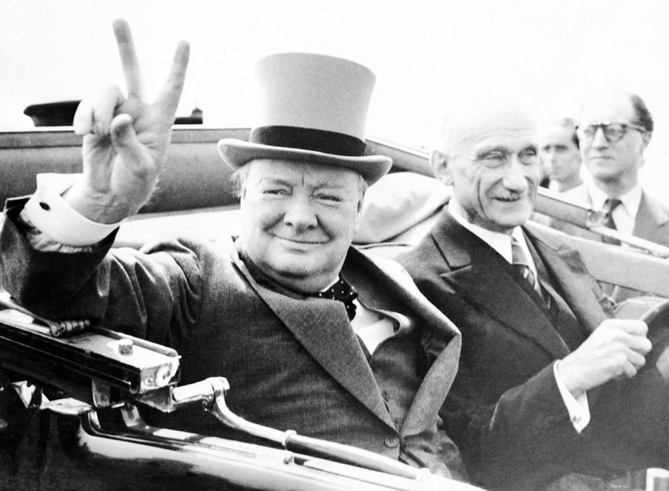 (AP file photo) FILE - Former British Prime Minister Winston Churchill gives his world famous V-sign, as he drives through Metz, France, during Bastille Day celebrations on July 14,1946.