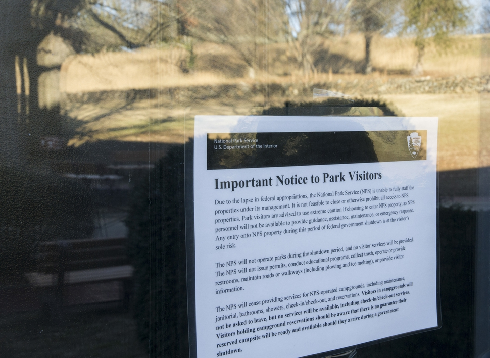 A sign is posted at the Fredericksburg and Spotsylvania National Military Park in Fredericksburg, Va. on Saturday, Jan. 20, 2018 advising visitors that some services would be unavailable due to a government shutdown. Reflected in the window is the Sunken Road, the site of fierce fighting during the Battle of Fredericskburg in 1862. (Mike Morones/The Free Lance-Star via AP)