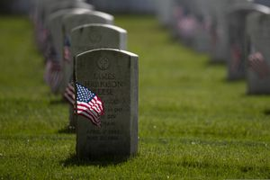 """American flags are placed by members of the 3rd U.S. Infantry Regiment, also known as The Old Guard, in front of each headstone for """"Flags-In"""" at Arlington National Cemetery in Arlington, Va., Thursday, May 21, 2020, to honor the Nation's fallen military heroes. (AP Photo/Carolyn Kaster)"""