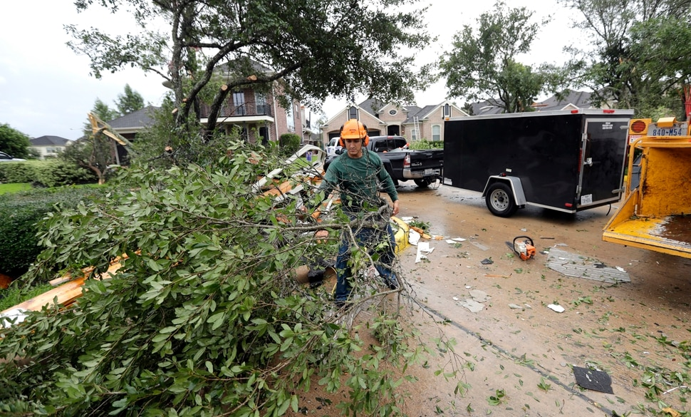(David J. Phillip | The Associated Press) Henry Isaac removes broken tree limbs after Hurricane Harvey Saturday, Aug. 26, 2017, in Missouri City, Texas. Harvey rolled over the Texas Gulf Coast on Saturday, smashing homes and businesses and lashing the shore with wind and rain so intense that drivers were forced off the road because they could not see in front of them.
