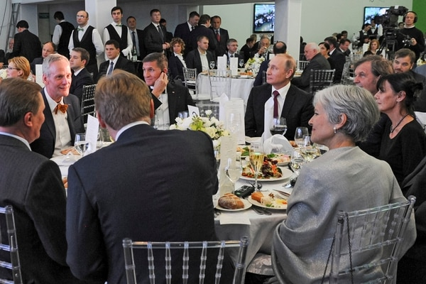 FILE- In this file photo taken on Thursday, Dec. 10, 2015, Russian President Vladimir Putin, center right, with retired U.S. Lt. Gen. Michael T. Flynn, center left, and Serbian filmmaker Emir Kusturica, obscured second right, attend an exhibition marking the 10th anniversary of RT (Russia Today) 24-hour English-language TV news channel in Moscow, Russia. The Kremlin said Monday Dec. 4, 2017 that conversations between the Trump administration and the Russian ambassador to the United States could not have possibly swayed Putin's decision on U.S. sanctions imposed by the outgoing administration. (Mikhail Klimentyev/Sputnik, Kremlin Pool Photo via AP, file)