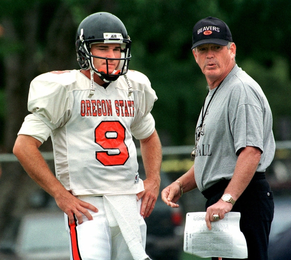 (AP Photo/Don Ryan, File) In this Wednesday, Aug. 18, 1999 file photo, Oregon State head football coach Dennis Erickson talks strategy with quarterback Jonathan Smith during practice in Corvallis, Ore.