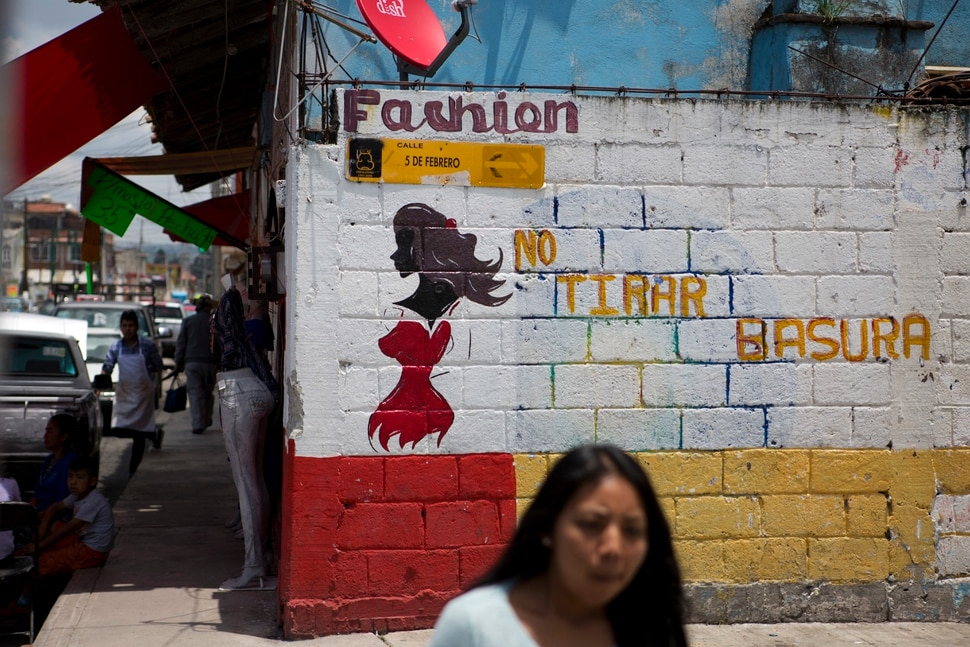 In this Aug. 18, 2017 photo, a woman walks past the wall of a clothing store painted with the figure of a woman as advertising, next to phrase