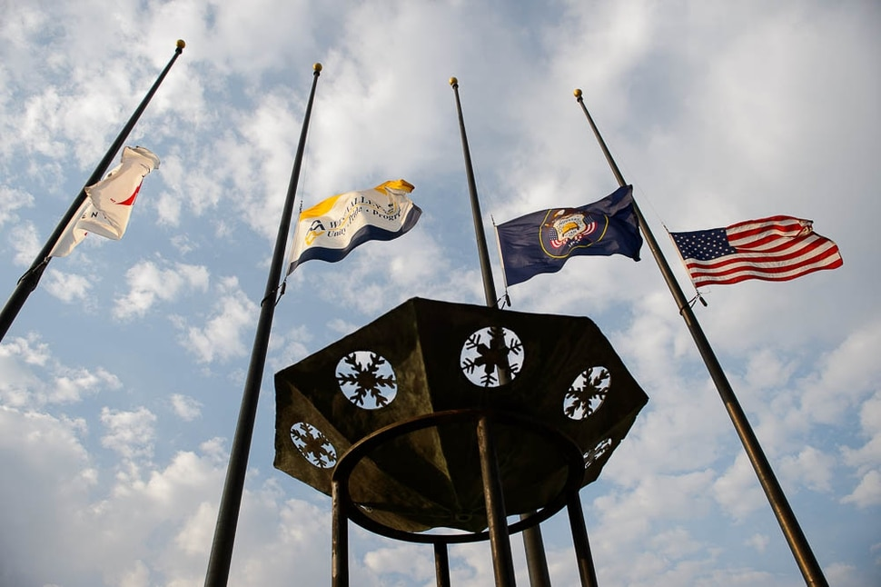 (Trent Nelson | The Salt Lake Tribune) Flags fly at half mast at the funeral services for Battalion Chief Matthew Burchett at the Maverik Center in West Valley City, Monday Aug. 20, 2018.