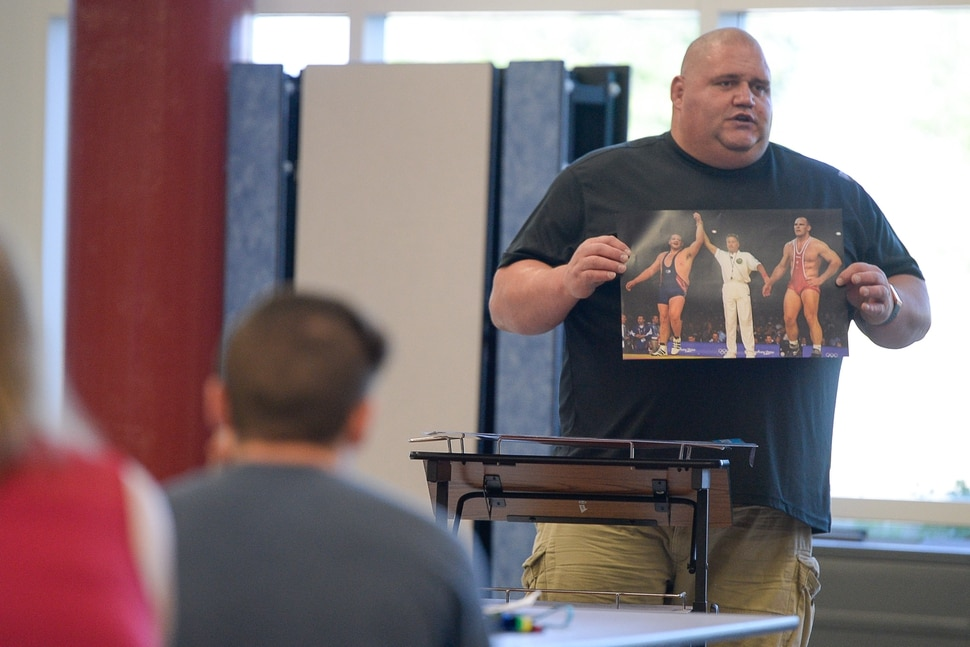 (Francisco Kjolseth | The Salt Lake Tribune) Olympic wrestling champion Rulon Gardner displays a photo of his historic upset over Russian Aleksandr Karelin for the gold medal during the 2000 Sydney Olympics as he meets with students and parents on Wed. May 16, 2018, to introduce himself as the new wrestling coach at Herriman High school.