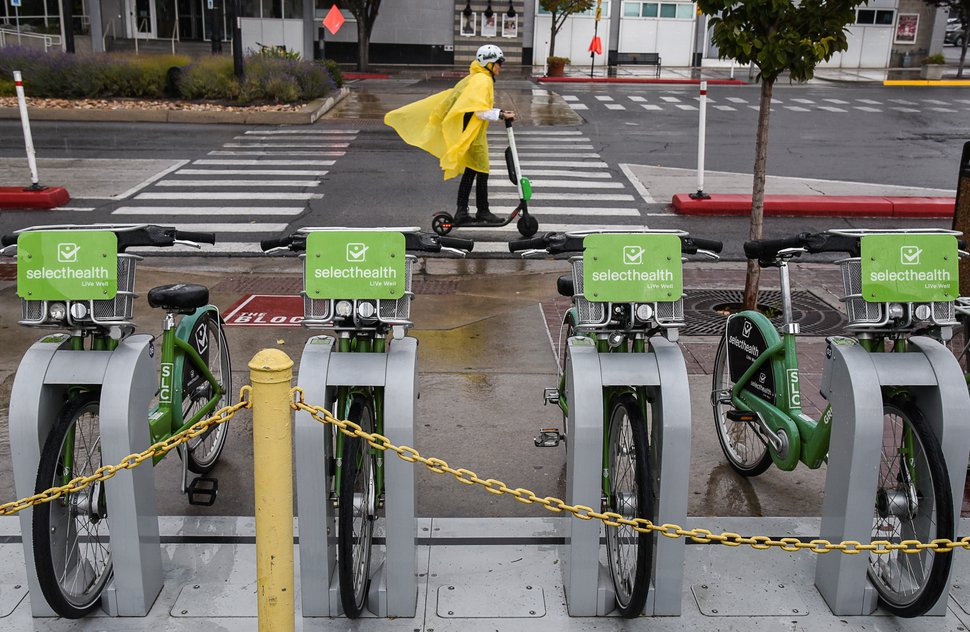(Francisco Kjolseth | Tribune file photo) An electric scooter rider braves the rain in downtown Salt Lake City, Oct. 2, 2108. Scooter and bikes available for rent are cutting into short-hop transit rides.