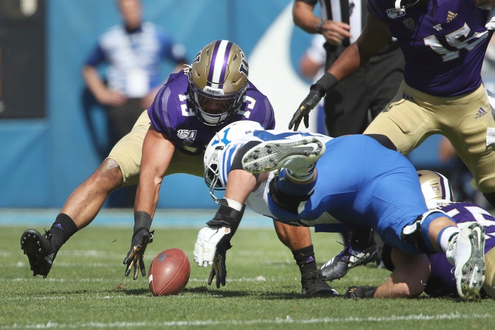 Washington linebacker Brandon Wellington (13) gathers a loose ball from BYU offensive lineman Tristen Hoge (69) in the first half, during an NCAA college football game, Saturday, Sept. 21, 2019, in Provo, Utah. (AP Photo/George Frey)