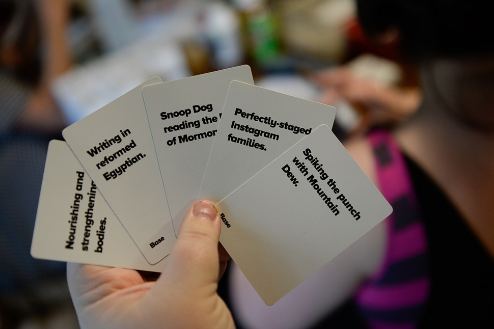 (Francisco Kjolseth | The Salt Lake Tribune) Spiking the punch with Mountain Dew, Dang You to Heck, billed as a family-friendly, Utah-themed alternative to Cards Against Humanity and other NSFW card games is the creation of Jerilyn Pool, of Provo, with an assist from her husband Jeff as they assemble themed collections at their home on Thursday, Aug. 3, 2018.
