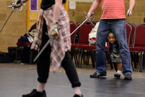 Trent Nelson  |  The Salt Lake Tribune With his daughter, London, between his legs, Jared Larkin teaches a stage combat class at Salt Lake School for the Performing Arts, Tuesday, June 2, 2015. Working on a fight routine are students Gerard Black and Hana Neves.