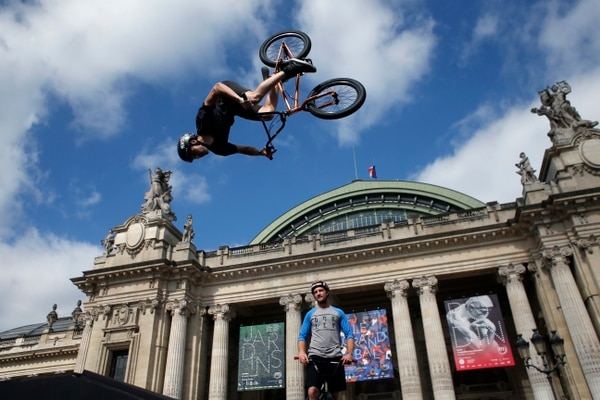 Belgian biker Kenneth Tancre performs outside the Grand Palais museum in Paris, Friday, June 23, 2017. Paris is aiming to boost its bid for the 2024 Olympics by turning some of its world-famous landmarks over to sports for two days, with 100-meter races on a track floating on the Seine, high-diving into the river, cycling around the Arc de Triomphe and other events to showcase the French capital's suitability for the games. (AP Photo/Thibault Camus)