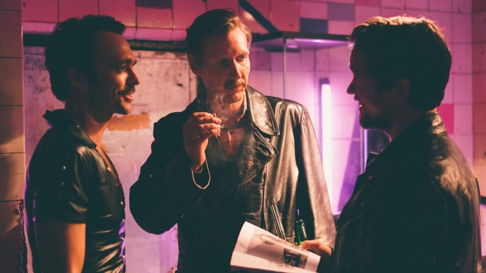 (Josef Persson | courtesy Kino Lorber Films) Finnish artist Touko Laaksonen (Pekka Strang, center), whose drawings inspired the gay leather lifestyle, meets two of his American fans (Seumas Sargent, left, and Jakob Oftebro) in the biographical drama Tom of Finland.