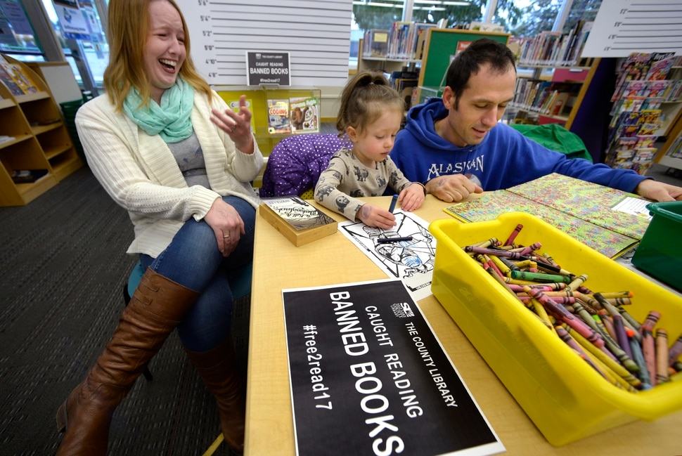 (Scott Sommerdorf | The Salt Lake Tribune) Jessica Quarles, left sits with her 3 year old daughter Signy as her husband Leighton Quarles reads Where's Waldo during the banned book event at the County LibraryÕs Smith branch, Sunday, September 24, 2017. The public was invited to bring their favorite banned book to the Smith branch and participate in a Facebook live event where they would all read from their banned books, simultaneously, for approximately three minutes in celebration of our intellectual freedom.