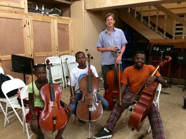 Yuki MacQueen | Courtesy Utah Symphony musicians John Eckstein (tall man in blue shirt), Yuki MacQueen (woman in white top) and James Hall (man in white shirt) worked with music students in Haiti this summer and will return in the spring with several of their colleagues and music director Thierry Fischer.