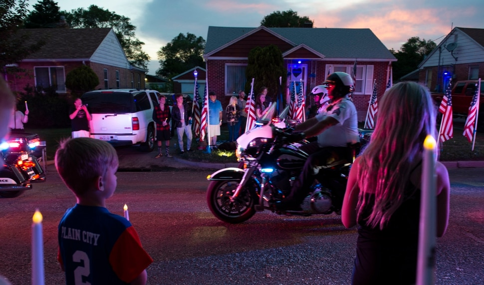 (Leah Hogsten | The Salt Lake Tribune) Ogden Police Department vehicles drive past Officer Nate Lyday's childhood home on Custer Avenue in Ogden in a Memorial Procession and Community Vigil in honor of Lyday's life. The procession made its way through five other Ogden landmarks before ending at Lindquist Field.