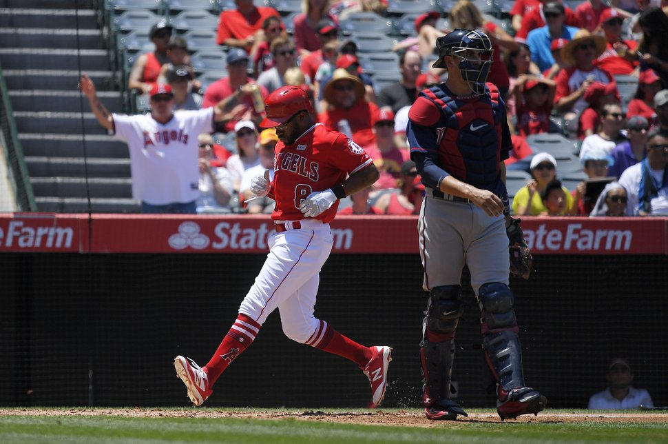 Los Angeles Angels' Eric Young Jr., left, scores after Andrelton Simmons grounded into a double play as Minnesota Twins catcher Jason Castro, right, stands at the plate during the third inning of a baseball game, Sunday, June 4, 2017, in Anaheim, Calif. (AP Photo/Mark J. Terrill)